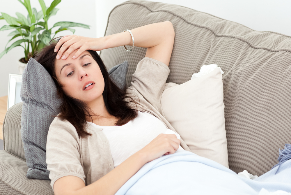 Indisposed woman feeling her temperature while resting on the sofa at home