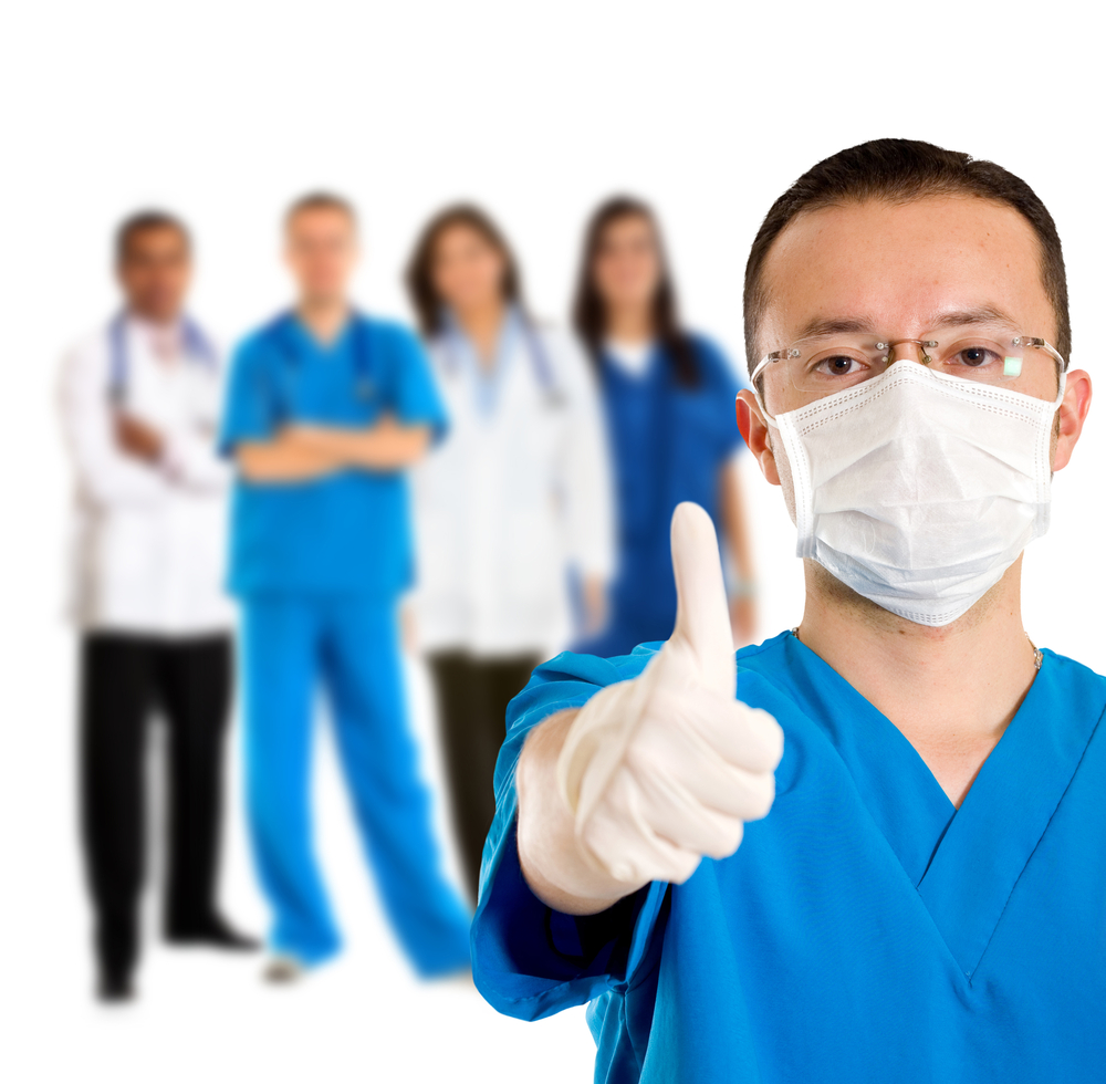 Surgeon with thumbs up and doctors behing him, isolated